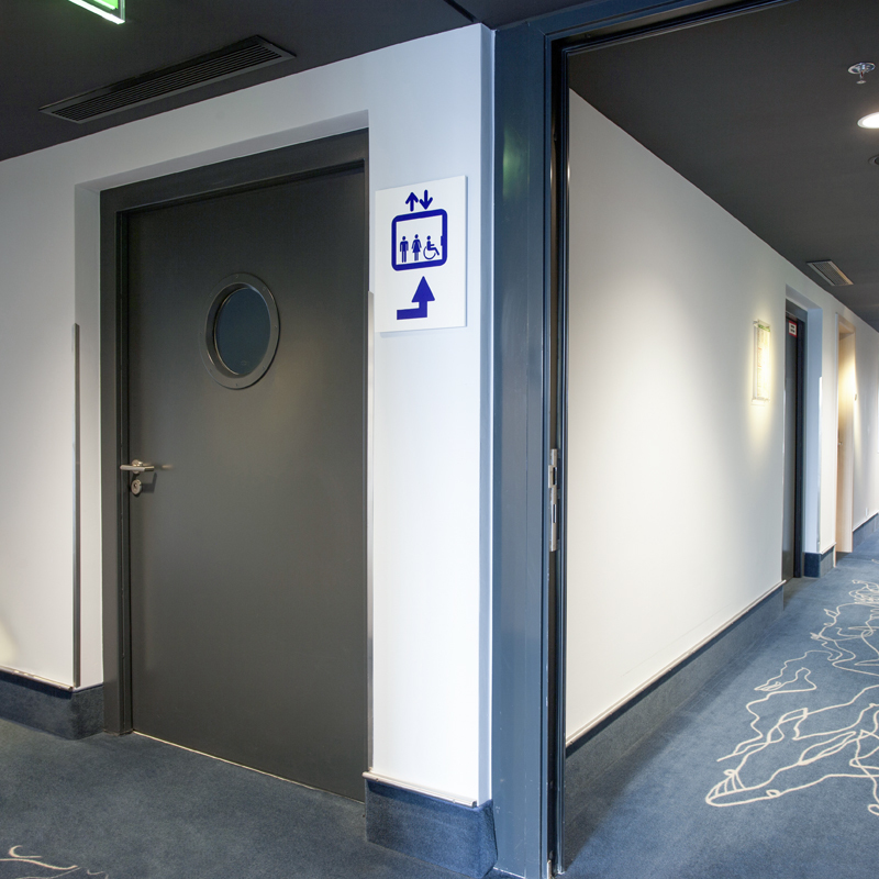 Steel Fire Door with Porthole Window Protecting A Hotel Corridor